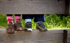 children feet standing on a wooden fence